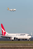 Qantas Boeing 737-800 aircraft at Sydney Airport with a Tiger Airways Airbus A320 on approach in the background. stock photo