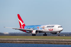 Qantas Boeing 767 airliner with special markings to promote the Disney Planes movie taking off from Sydney Airport. Royalty Free Stock Image