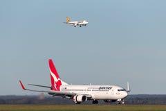 Qantas Boeing 737-800 flygplan på Sydney Airport med en Tiger Airways Airbus A320 på inställning i bakgrunden Royaltyfri Foto
