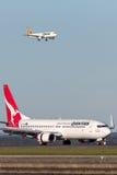 Qantas Boeing 737-800 flygplan på Sydney Airport med en Tiger Airways Airbus A320 på inställning i bakgrunden Arkivfoto
