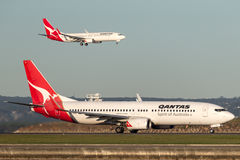 Qantas Boeing 737 at Sydney Airport with another Qantas 737 landing in the background. Stock Photo
