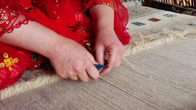 Qashqai kobieta w czerwieni ciie dywan podczas gdy wyplatający zbliżenia zwolnione tempo zbiory
