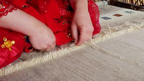 Qashqai woman in red weaves carpet closeup slow motion.  stock video