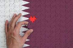 Qatar flag is depicted on a puzzle, which the man`s hand completes to fold.  royalty free illustration