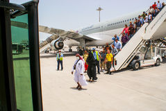 Qatar. May 2009. Passengers disembark from the aircraft Qatar Ai. Rways at the airport of Doha. In the foreground a woman in a niqab and a man in Muslim clothes Stock Images