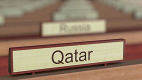 Qatar name sign among different countries plaques at international organization. 3D rendering Royalty Free Stock Photography