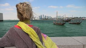 Woman at Doha Skyline. Qatar travel concept. Carefree caucasian woman enjoyis the traditional dhow boats of Doha West Bay. Blonde tourist at Doha Downtown from stock video