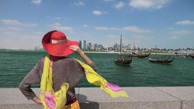 Woman at Doha Skyline. Qatar travel concept. Elegant caucasian woman enjoyis the views of Doha West Bay. Blonde tourist at Doha Downtown from East Mound-Skyline stock footage