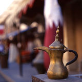 Qatar welcome. A coffee pot - the Arab symbol of welcome - in front of a Qatari flag in Souq Waqif, Doha, Qatar. The souq is one of Qatar's main tourist stock images