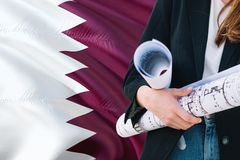 Qatari Architect woman holding blueprint against Qatar waving flag background. Construction and architecture concept.  stock photography