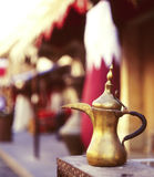 Qatari coffee pot welcome. A traditional old brass coffee pot in front of a Qatari flag in Souq Waqif, Doha. The coffee pot, or dallah, symbolises welcome in Stock Images
