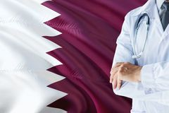 Qatari Doctor standing with stethoscope on Qatar flag background. National healthcare system concept, medical theme.  royalty free stock photo