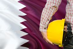 Qatari Engineer is holding yellow safety helmet with waving Qatar flag background. Construction and building concept.  royalty free stock photography