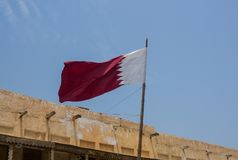 Qatari Flag flying over traditional Arabic building. Qatari Flag blowing in the breeze over a traditional Arabic building located in Souq Waqif which is in Doha stock photo