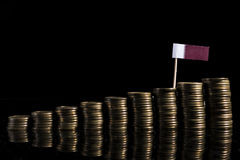 Qatari flag with lot of coins on black. Background stock photo