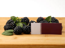 Qatari flag on a wooden panel with blackberries isolated on a wh. Ite background Royalty Free Stock Photos