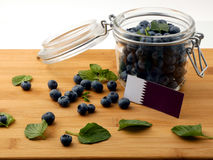 Qatari flag on a wooden plank with blueberries on white. Qatari flag on a wooden plank with blueberries royalty free stock photography