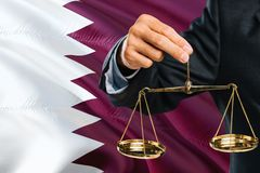Qatari Judge is holding golden scales of justice with Qatar waving flag background. Equality theme and legal concept.  stock images