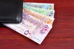 Qatari money in the black wallet. On a wooden background stock image