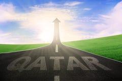 Qatariskt ord med pilen uppåt på vägen Royaltyfria Foton