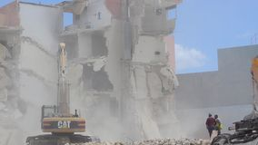 Qawra, Malta 16. may 2019 - Second day of demolishing old Qawra Inn hotel - demolishing building with excavator and. Supervisors are not wearing protective stock video