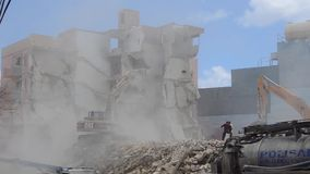 Qawra, Malta 16. may 2019 - Second day of demolishing old Qawra Inn hotel - demolishing building with excavator and. Supervisors are not wearing protective stock video footage
