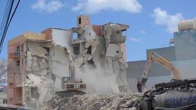 Qawra, Malta 16 podem 2019 - segundo dia de demulir o hotel velho da pens?o de Qawra - demoli??es da constru??o com m?quina escav video estoque