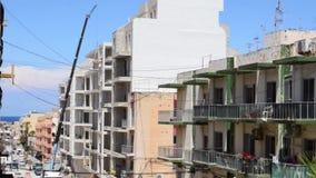 Qawra, Malta 14 podem 2019 - trabalhadores da constru??o no local, elevador que levanta acima dos sacos com cimento em Flor super video estoque
