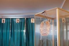 Qazaqstan, 9-ое июня 2019, избрание президента Казахстана Голосуя комната Прозрачная коробка с гербом на стоковые фотографии rf