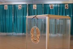 Qazaqstan, 9-ое июня 2019, избрание президента Казахстана Прозрачная коробка с эмблемой Голосуя комната на предпосылке стоковые фото