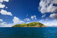 QE Island Hill. Green hill island blue coral sea under cloudy sky tropical idilly Royalty Free Stock Photos