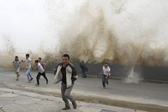 Qiantang tide. People run when waves jumped over the dam caused by qiantang tide Royalty Free Stock Images