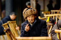 Qianwei China-An old man is smoking Royalty Free Stock Images