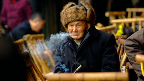 Qianwei China-An old man Spit smoke Stock Photography