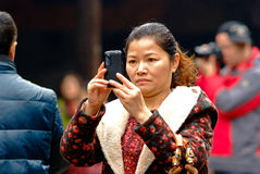 Qianwei China-A women is taking photos Stock Photography