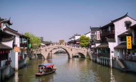 Qibao Shanghai, Kina - April 7,2012: Qibao vattenby, fartyg i den huvudsakliga kanalen och en gammal bro Royaltyfria Foton