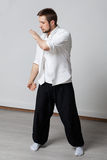 Qigong training. Practice. Qigong. Young man in white shirt and black pants performing tai chi exercise Royalty Free Stock Images