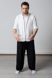 Qigong training. Practice. Young man in white shirt and black pants performing tai chi exercise Royalty Free Stock Images