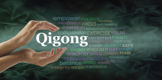 Qigong word cloud and healing hands. Female cupped hands with the word QIGONG between surrounded by word cloud on a flowing green light and dark background Royalty Free Stock Photo