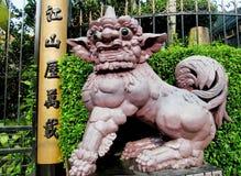 Qilin asian mythological statue near hieroglyphic column Stock Photos
