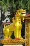 Qilin asian mythological guard goolden statue in Thailand wat. Qilin asian mythological statue in the yard of Thailand wat thai buddhist temple near big stupa Royalty Free Stock Photo