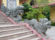 Qilin small dragon statue at temple stairs. Qilin asian stone mythological statue in the yard. Chinese and vietnam ancient mythological magic creature. a stock image