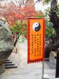 Qingdao, China - em dezembro de 2017: Bandeira alaranjada vibrante com um yin y imagens de stock royalty free