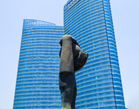 Qingdao city between heaven and earth Sculpture. A hand and a let holding a ball statue called between heaven and earth with urban office buildings in qingdao stock images