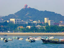Qingdao sightseeing boats on the sea. Qingdao pleasure-boats and speedboats on the sea with island background in Shandong province China Stock Image