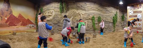 Kid excavating dinosaur fossil on sand. QingYuan China December 31,2018:kid excavating dinosaur fossil on sand royalty free stock images