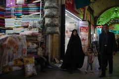 Famous Iranian market bazaar and a woman in a black chodor walking down a textile street with her husband and son royalty free stock photos