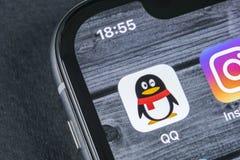 QQ信使在苹果计算机iPhone x智能手机屏幕特写镜头的应用象 QQ信使app象 黑板企业白垩黑板画媒体网络网络连接人照片社交的概念连接数 免版税库存照片