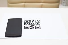 Qr-código y smartphone en la tabla en casa fotografía de archivo