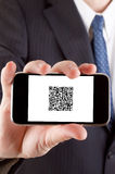 QR Code. Businessman showing us a touch phone with a qr code against a white background Royalty Free Stock Photography